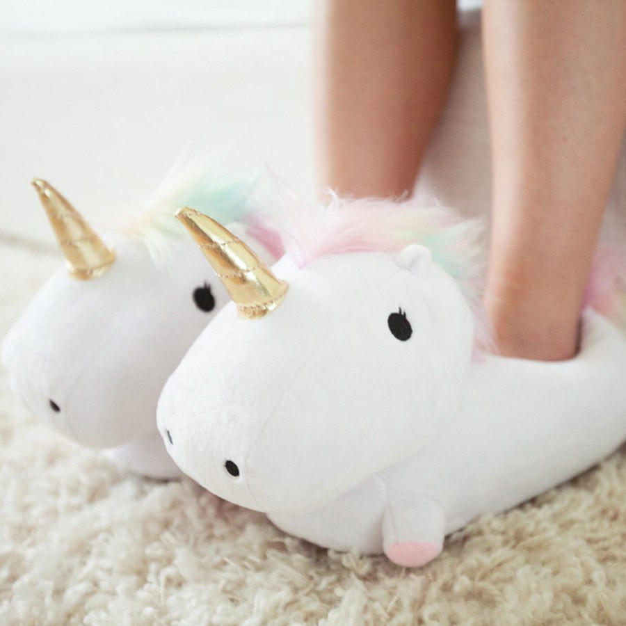 unicorn slippers with a gold horn and rainbow mane on a cream rug. bare legs in the slippers