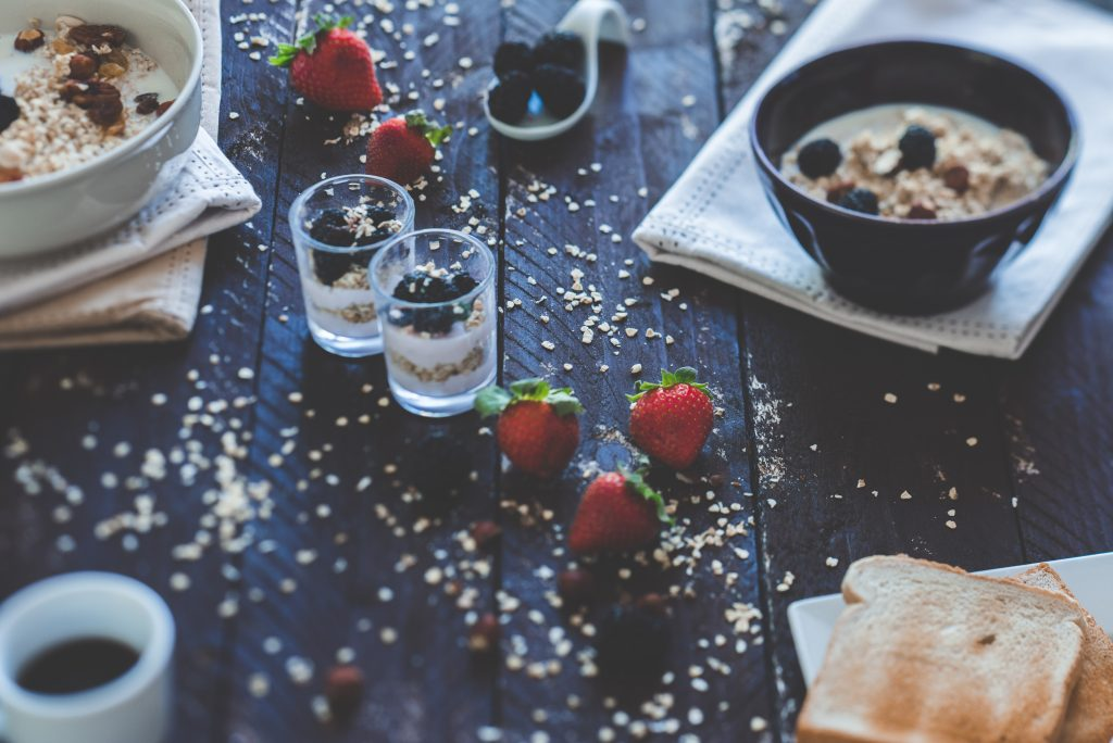 a dark wood breakfast table scattered with various breakfast food and strawberries with bowls of oats and blueberries