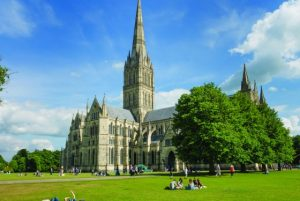 a sunny day with blue sky and few white clouds at salisbury cathedral which has a tall spire and is grey with trees next to it on the right and a green lawn in front with people sitting all over it