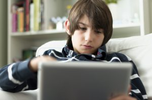 a brunette boy of about 12 sat on a white chair with a silver laptop open on his lap looking at the screen with a bookcase behind him out of focus