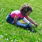 Alyssa on the grass picking daisies