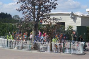 an art display of ceramic and glass trees and flowers that are actually a fountain surrounded by wrought iron fence and people walking past