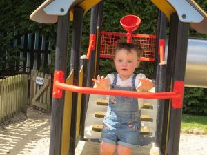 Alyssa wearing denim dungarees and white tshirt with hair in bunches grabbing a red bar above a slide