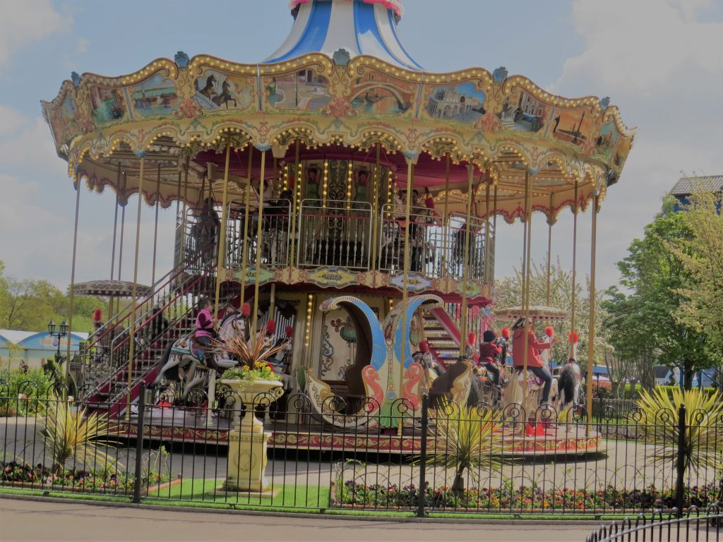 a traditional old Carousel with people riding the horses surrounded by a black wrought iron fence and a bit of grass