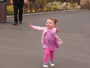 alyssa walking down a concrete path wearing all pink with her arms wide open