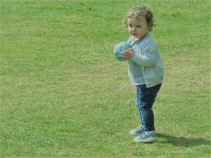alyssa in blue jeans and blue denim shoes a grey top and grey cardigan holding a small ball standing on the green grass on a sunny day