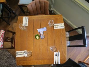 a top shot of a set table with cutlery napkins wine glasses a candle and menu in the middle and mismatched chairs