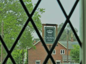 through a window that has a diamond pattern in lead lining. through the window you can see a tree and the sign for The Crown pub with a red brick house behind