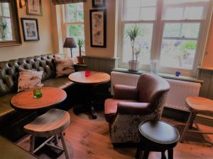 a wooden floor, a couple of round tables and different style chairs with cushions and windows with plants in them and pictures on the wall - the nook of the pub
