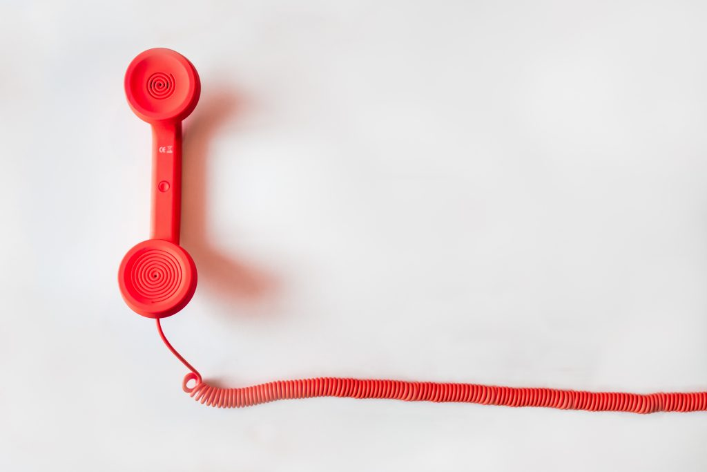 a white background with a red wire leading to a red telephone handle