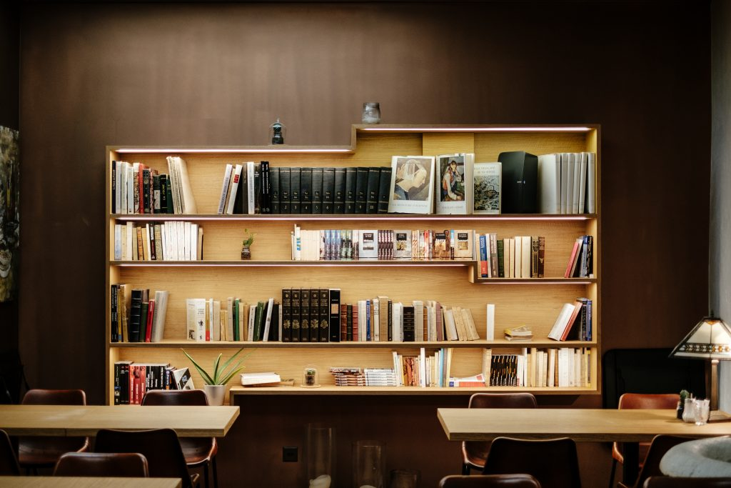 two wooden tables either side with chairs under and a semi full book case across the whole of the back of the picture and a dark wooden wall behind that