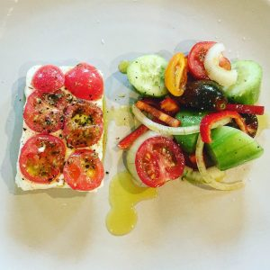 a block of feta cheese with slice tomatos on top and next to it a fresh greek salad with olive oil drizzled over it