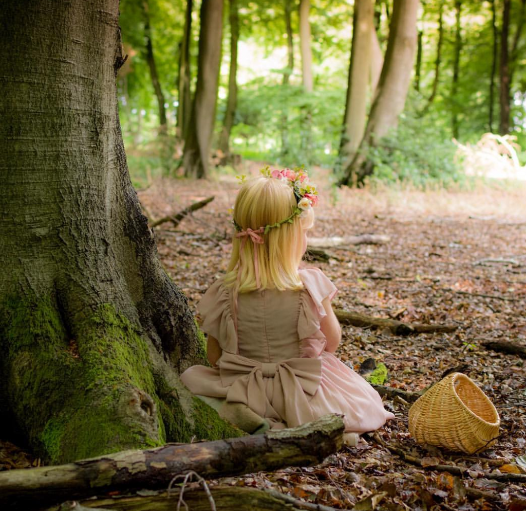 little blonde girl sat against the trunk of a tree in the woods with brown leaves on the floor wearing a crown of roses and a cream fairy dress and basket next to her facing away from the camera