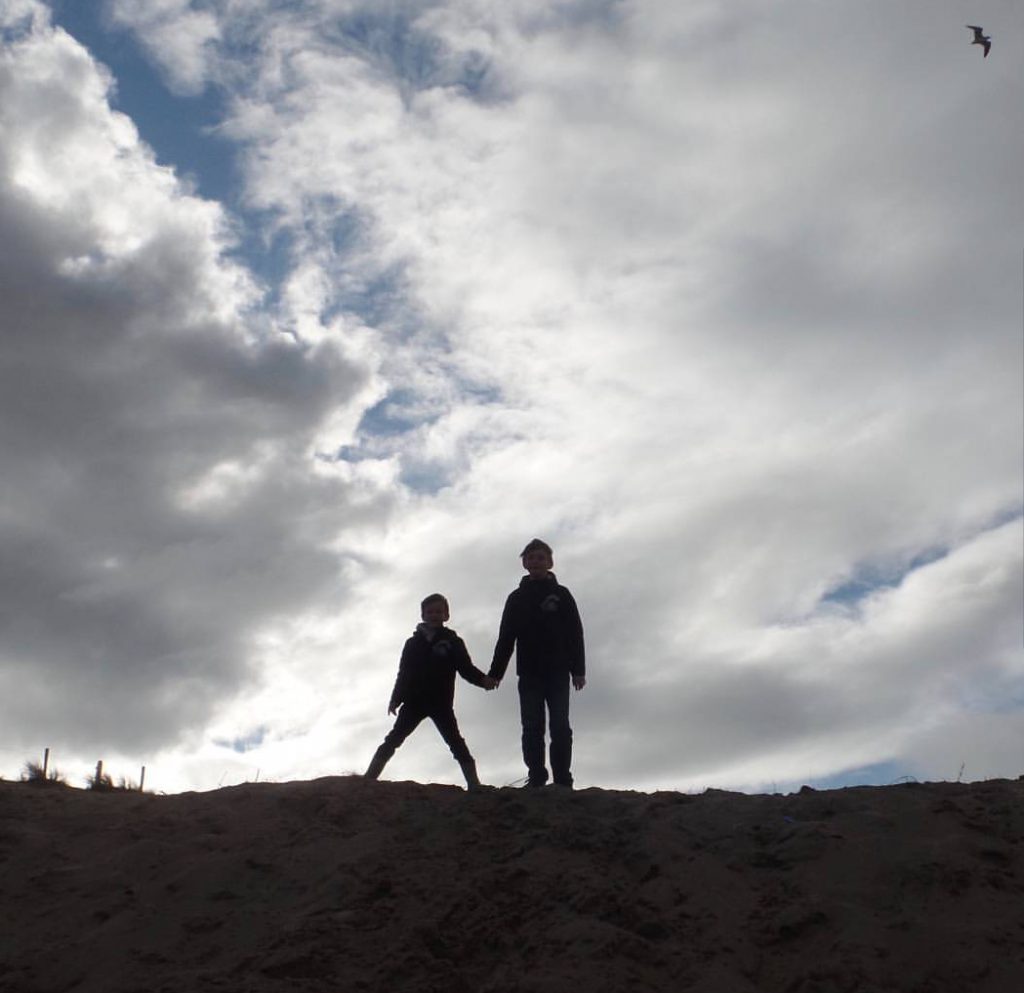 silhouette outline of two boys holding hands on top ofa hill with clouds blue sky and sun behind them