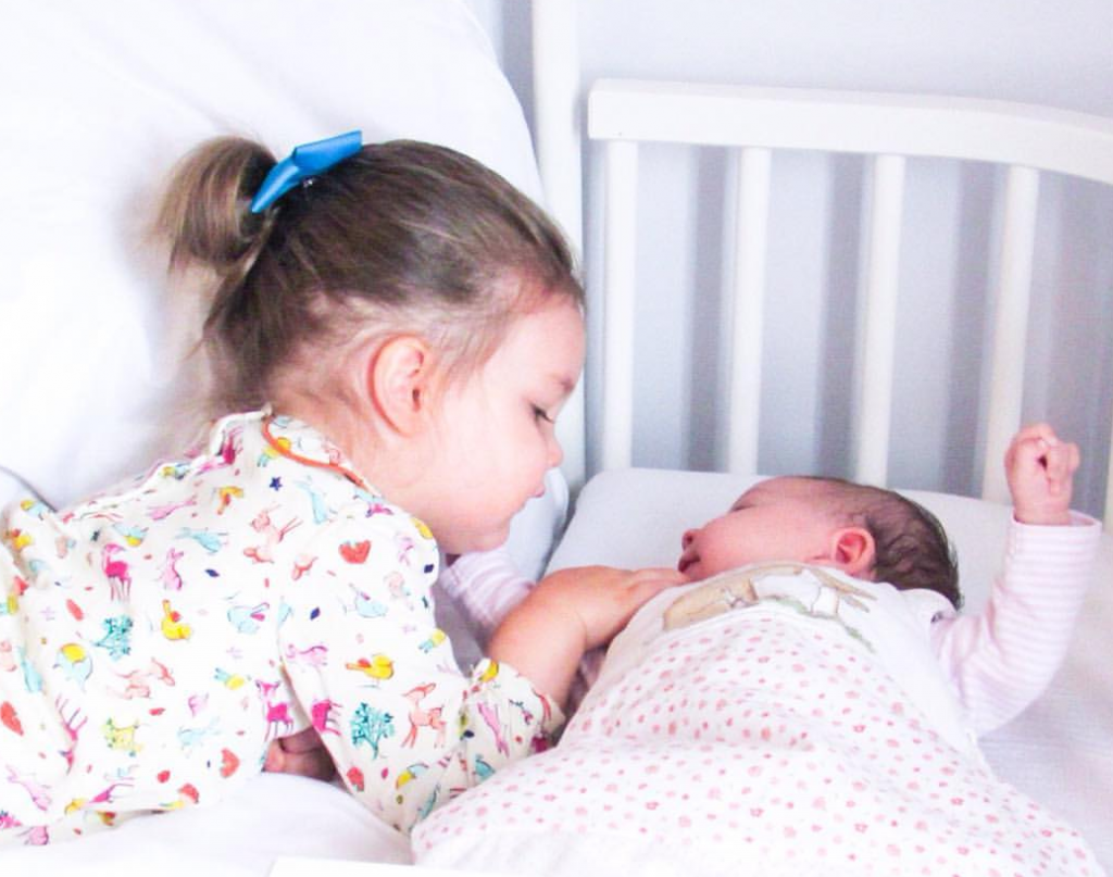 toddler girl with hair in ponytail wearing white babygro covered in primary coloured spots lying on a white bed frame next to a new born baby under a white blanket asleep