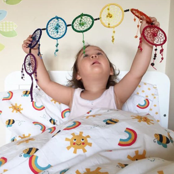 little brunette toddler sat up in bed white bed sheets with suns and rainbows on it she is holding up a rainbow coloured dream catcher