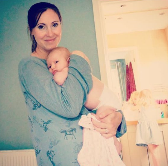 brunette woman wearing all blue hair in a ponytail standing looking at camera holding a very new baby with eyes open just wearing a nappy both looking at the camera with a little blonde girl back to camera playing in the background