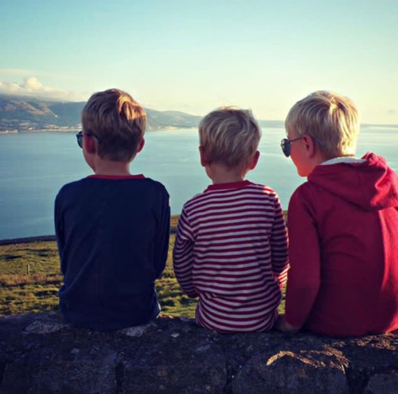 3 boys sat with their backs to camera on a green bank looking out at the blue sky and sea