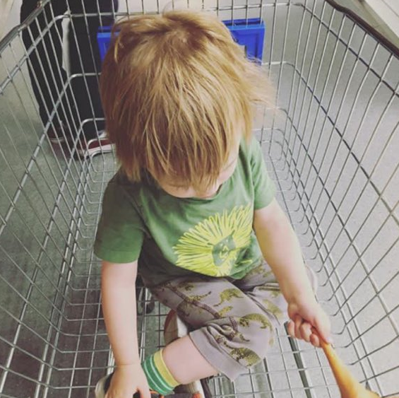 little blond boy with choppy hair head down in a green lion t-shirt, dinosaur leggings, green socks sat in an empty trolley
