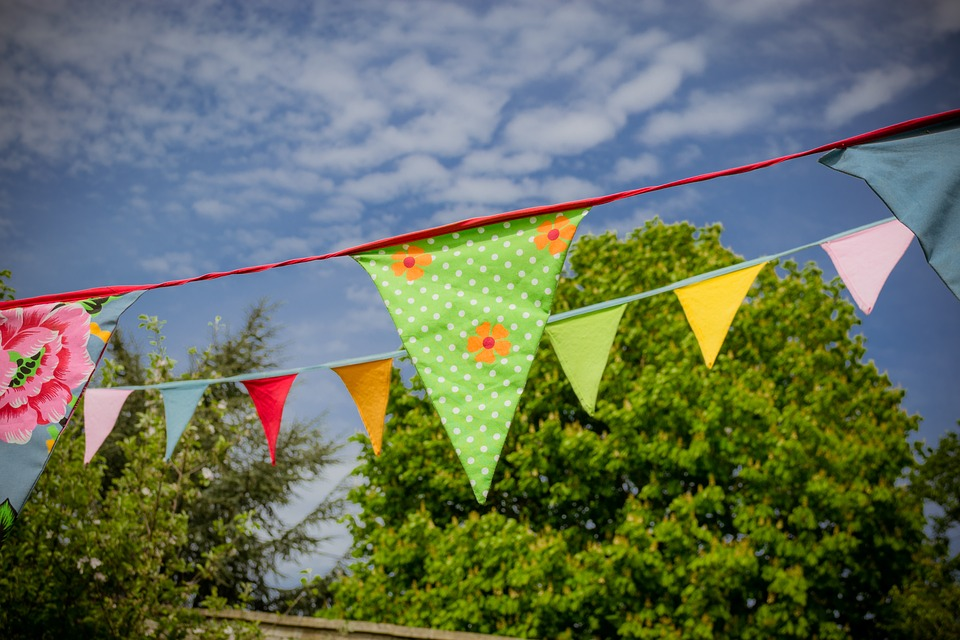 a string of bunting in green and yellow with blue sky above and trees behind