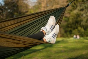 hammock hung up with white trainers hanging out and grass and trees in the background