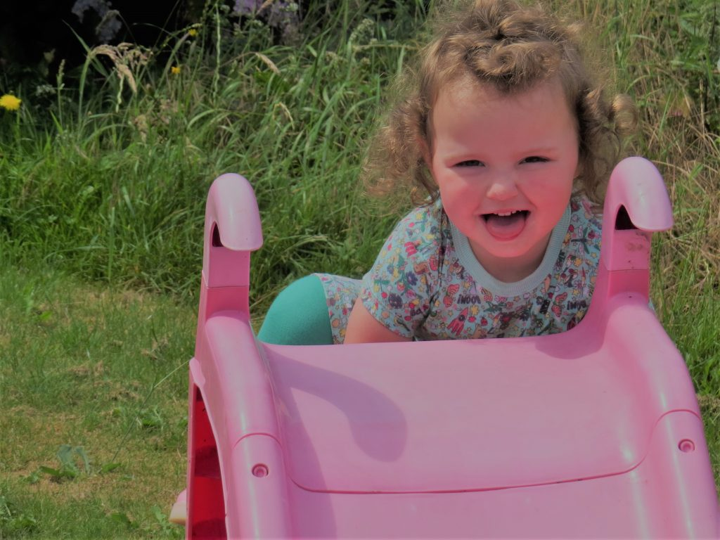 Alyssa in a green dress looking at the camera sticking her tongue out and smiling halfway up a pink slide with grass behind her