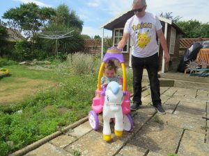 Alyssa satin the pink and purple little tikes horse and carriage with uncle pete behind in a garden