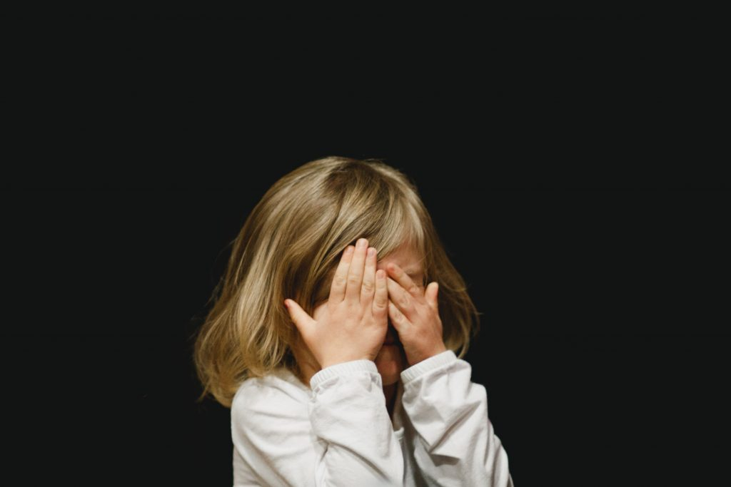 little girl with a blonde bob wearing a white jumper covering her face with her hands in front of a solid black background