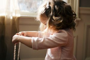 little girl with brown hair sideways on hair falling across her face in front of a window holding her mummy's pearl necklace