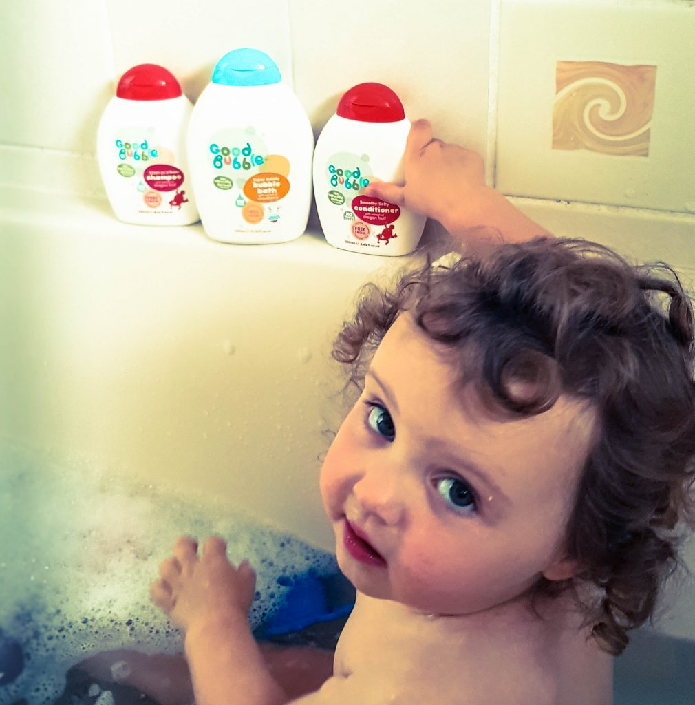 Alyssa in the bath with dry curly hair looking up at the camera with the three white and red bottles of bubble bath shampoo and conditioner lined up on the bath next to her