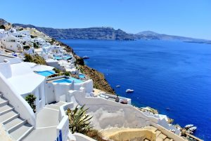a view over greece with white washed buildings on the left and blue sea on the right
