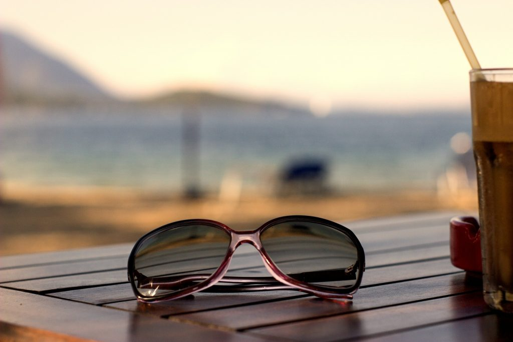 a pair of sunglasses on a wooden table with a blurred sea in the background