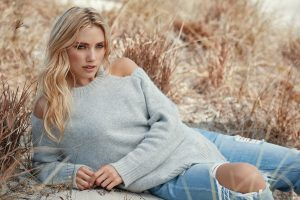 a blond woman wearing a grey jumper with cut out shoulders, jeans with ripped knees, lying in a corn field with blonde hair
