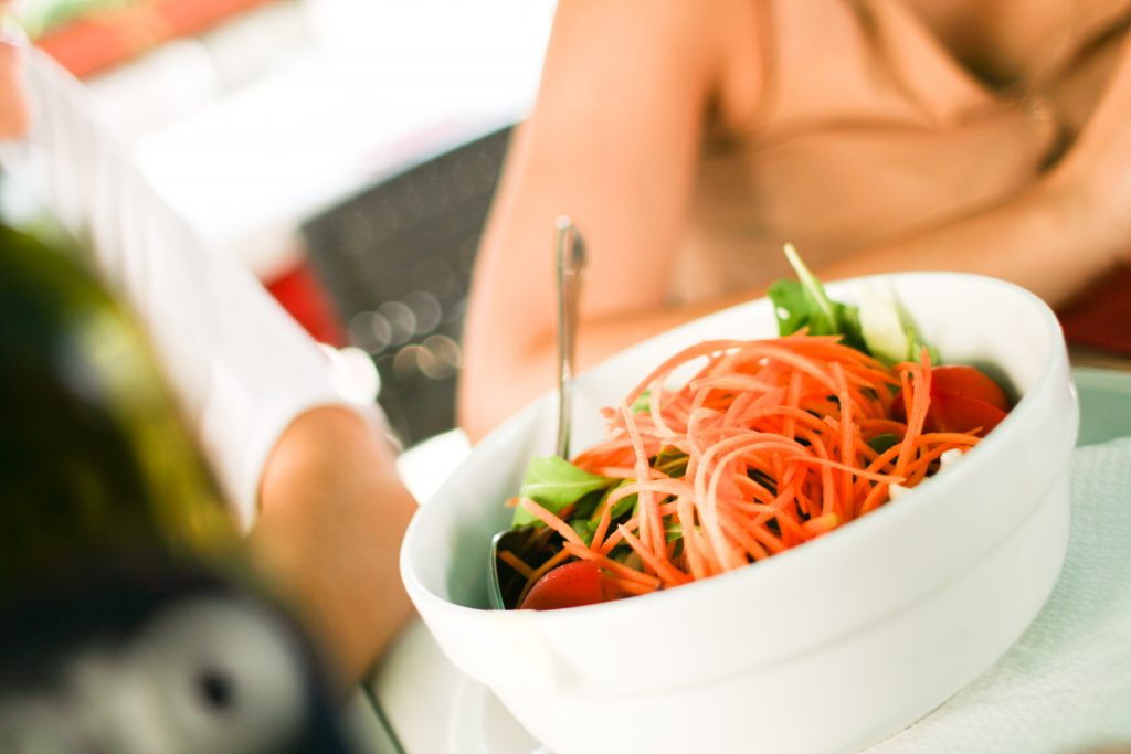 a white bowl with a heap of green leaves tomato and shredded carrot. a woman can be seen blurred in the background