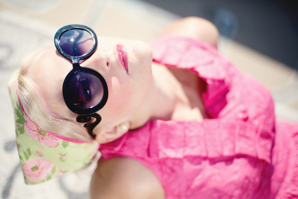 a woman in a pink dress wearing dark circle sunglasses leaning her head back and looking up at the sky