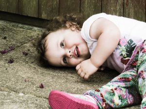 alyssa lying down on stones looking at the camera