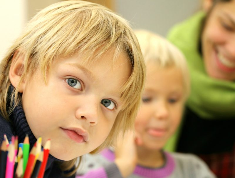 blonde boy and girl sat with pencils looking at the camera