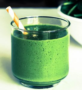 a small clear glass with a green drink inside and a striped straw sticking out to the left on a plain white table