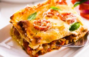 a white plate with a square of cooked cheesy vegetable lasagna and a fork next to it