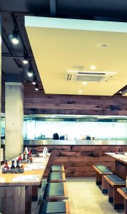 long white benches surrounded by wooden walls. a dropped ceiling with inset lighting and the camera is looking at the brightly lit open steel kitchen