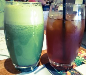 two tall clear glasses - one with a green juice concoction and the other with peach iced tea on a wooden table