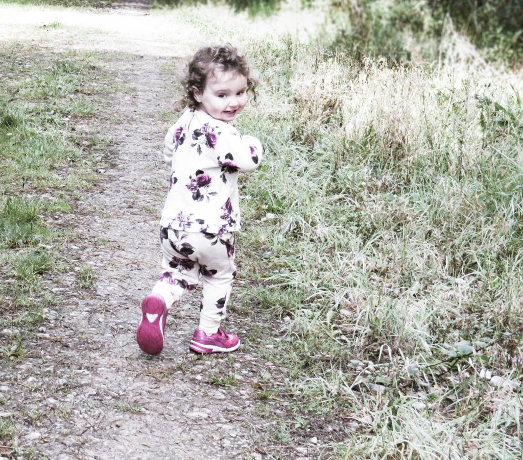 alyssa running away through some long grass with her head turned back smiling wearing the floral joggers and sweater