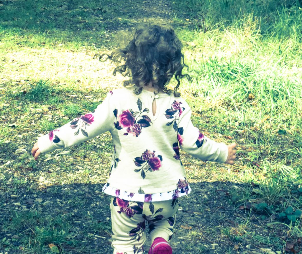 alyssa wearing the beige and pink floral jogger outfit running away from the camera down a woodland path