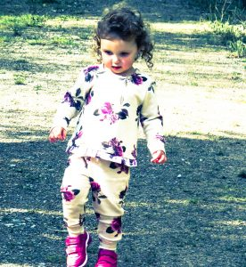 alyssa walking along the path looking down at the ground wearing the floral jump suit
