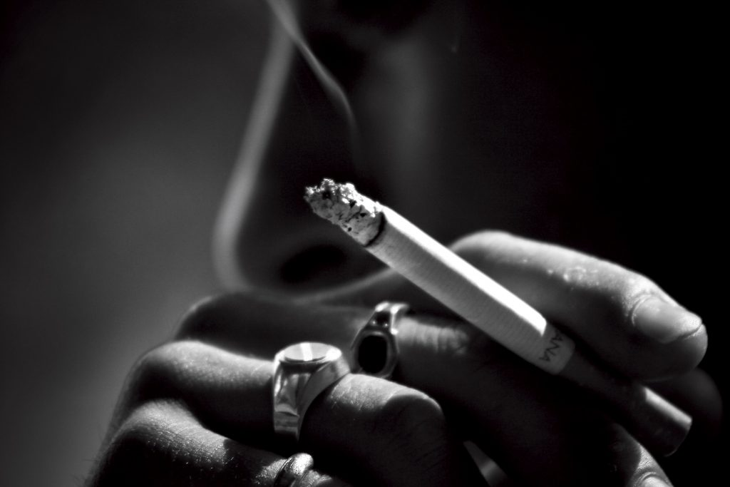 close up of a hand holding a smoking cigarette whole picture in black and white