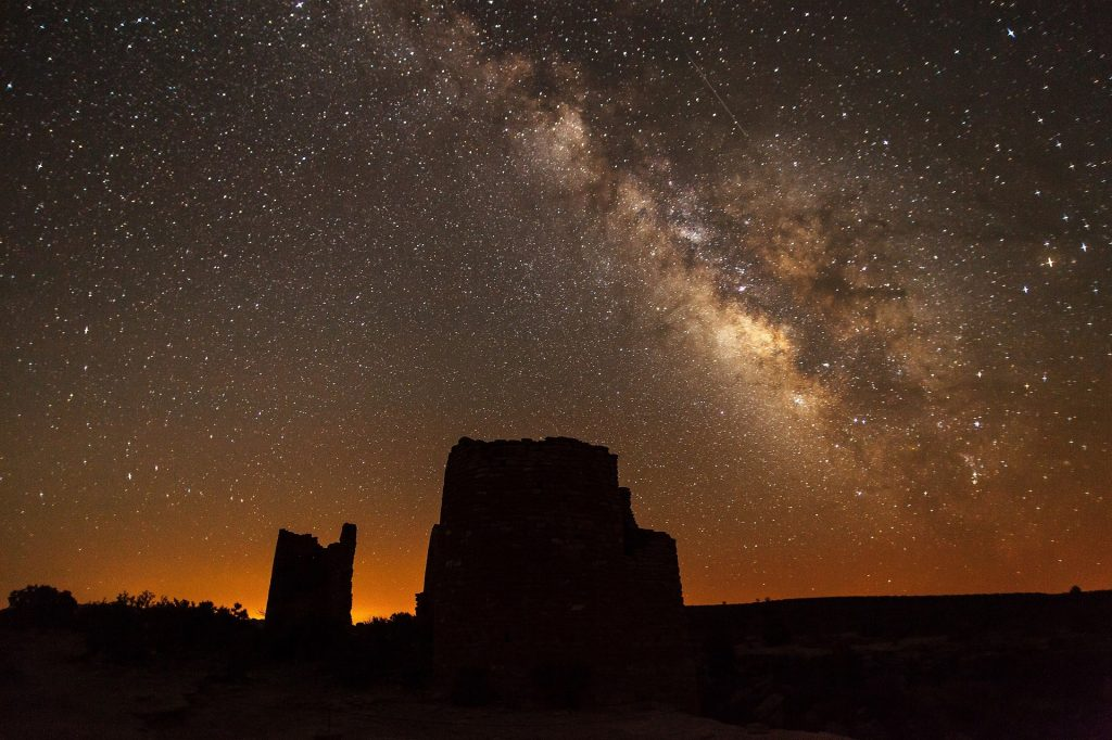 the milky way with the shadow of rocks on the ground