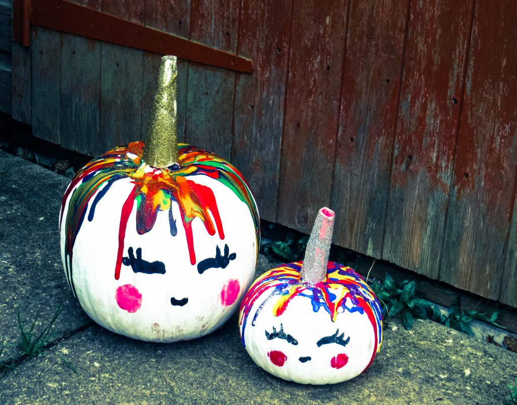 two pumpkins painted white with multi coloured paint dripped round and sparkly unicorn horns