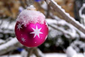 pink bauble hanging from a snowy branch