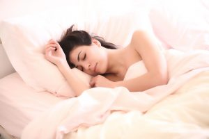 a brunette woman sleeping in a bed of white sheets