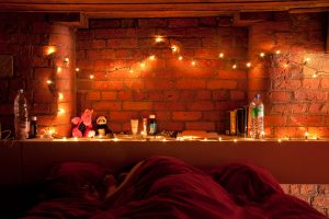 a brick wall with fairy lights on at the end of a bed with a red duvet on it